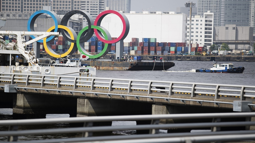 "Tugboats move a symbol installed for the Olympic and Paralympic Games Tokyo 2020 on a barge from its usual spot off the Odaiba Marine Park in Tokyo Thursday, Aug. 6, 2020. The five Olympic rings floating on a barge in Tokyo Bay were removed what is being called ""maintenance,"" and officials says they will return to greet next year's Games.  (AP Photo/Hiro Komae)."