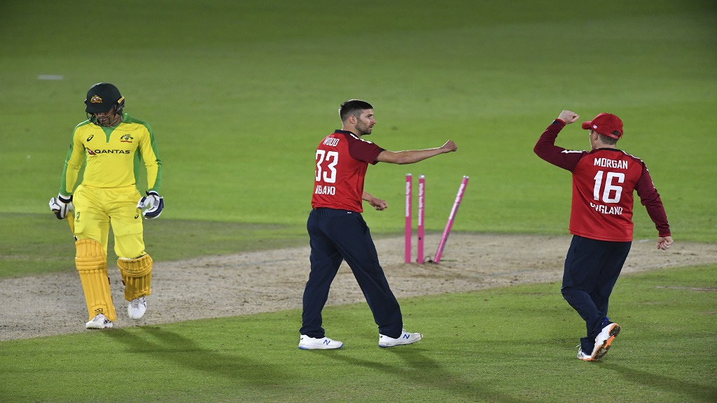 England's Mark Wood, centre, celebrates with captain Eoin Morgan, right, the dismissal of Australia's Alex Carey, left, during the first Twenty20 cricket match, at the Ageas Bowl in Southampton, England, Friday, Sept. 4, 2020. (Dan Mullan/Pool via AP).