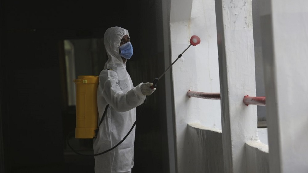 A worker sprays disinfectant in a school as preparations for reopening of educational institutions that were closed in March are finalized, in Karachi, Pakistan, Monday, Sept. 14, 2020. Education officials in Pakistan say authorities will start reopening educational institutions from Sept. 15 amid a steady decline in coronavirus deaths and infections. (AP Photo/Fareed Khan)