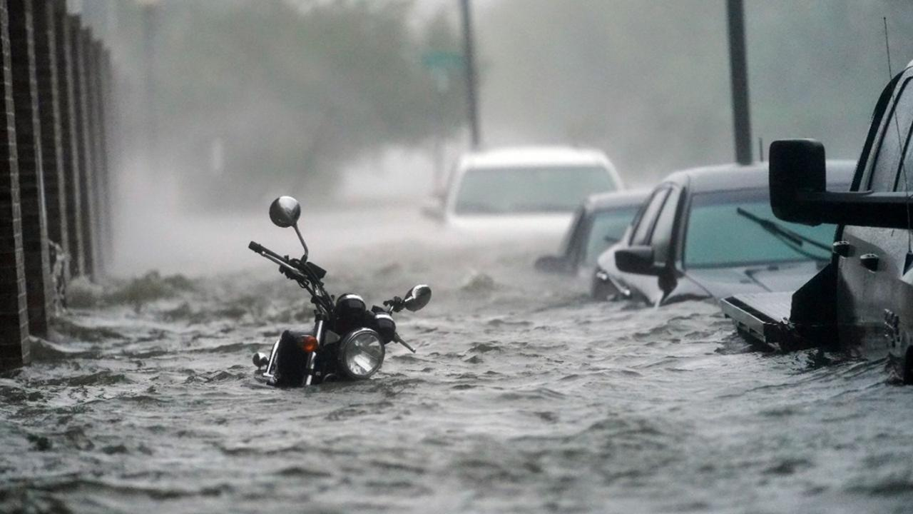 Cars and a motorcycle are underwater as water floods a street, Wednesday, September 16, 2020, in Pensacola, Florida.(AP Photo/Gerald Herbert)