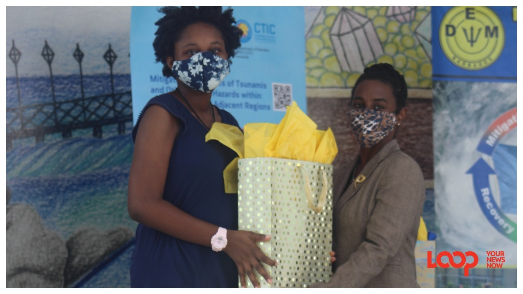 First place winner Kya Knight (l) of the Deighton Griffith School accepting her prize from Andrea White of the Ministry of Education, Technological and Vocational Training