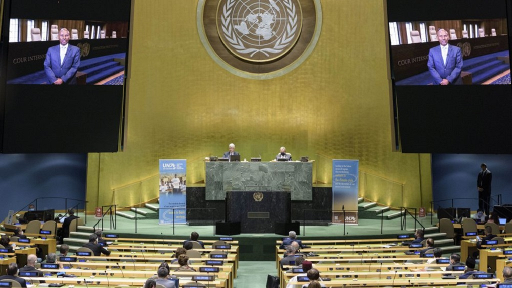 In this photo provided by the United Nations, President of the International Court of Justice, Judge Abdulqawi Ahmed Yusuf, is seen on screens as he addresses the United Nations General Assembly to commemorate the 75th anniversary of the United Nations. (Manuel Elías/United Nations via AP)