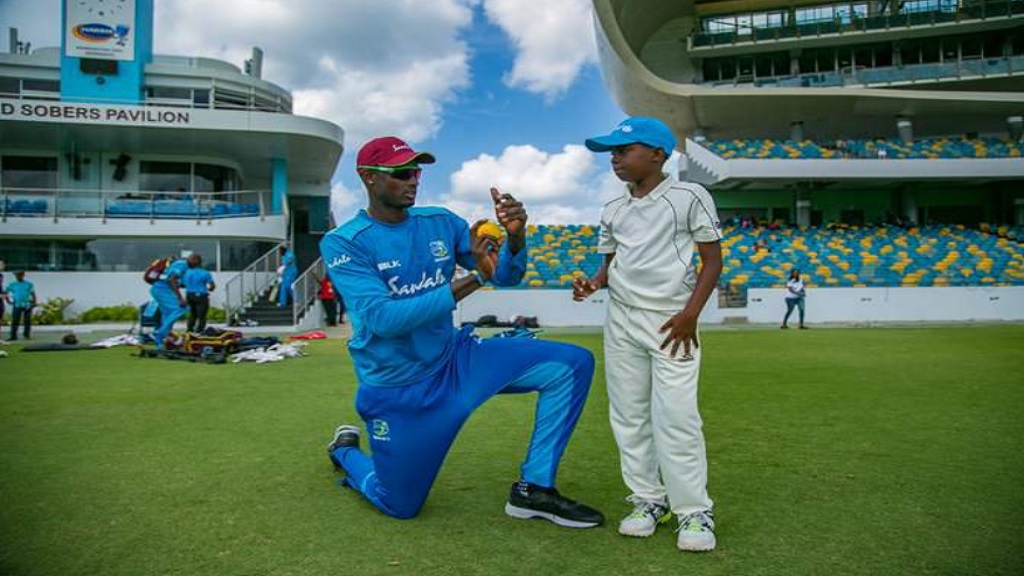 West Indies Test captain Jason Holder gives some tips to a young cricketer.