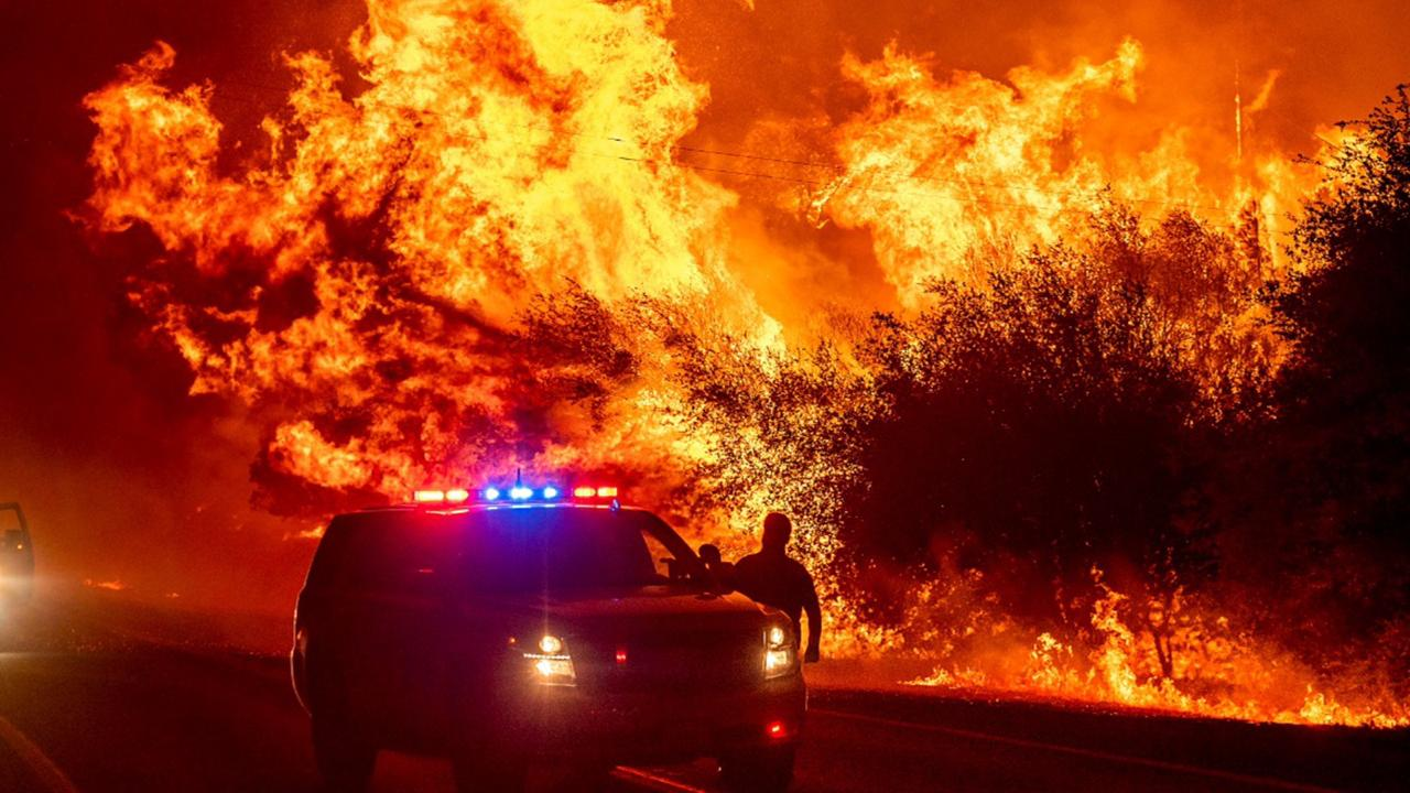 Flames lick above vehicles on Highway 162 as the Bear Fire burns in Oroville, California, on Wednesday, September 9, 2020. (AP Photo/Noah Berger)