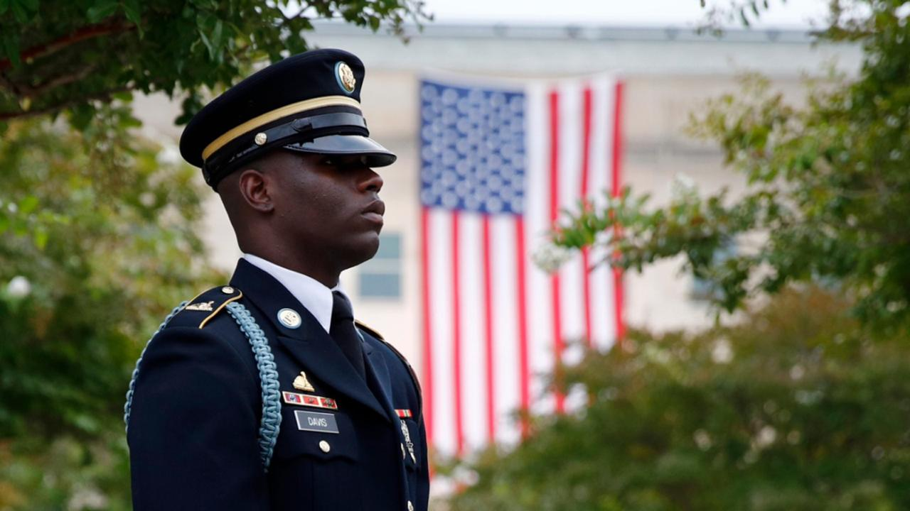 In this September 11, 2019, file photo, a member of the US Army Old Guard stands on the grounds of the National 9/11 Pentagon Memorial before a ceremony in observance of the 18th anniversary of the September 11th attacks at the Pentagon in Washington. On Sept. 11, 2020, Americans will commemorate 9/11 with tributes that have been altered by coronavirus precautions and woven into the presidential campaign. (AP Photo/Patrick Semansky, File)