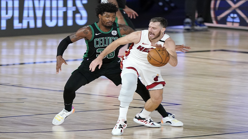 Boston Celtics' Marcus Smart, left, defends as Miami Heat's Goran Dragic, front, handles the ball during the second half of an NBA conference final playoff basketball game, Tuesday, September 15, 2020, in Lake Buena Vista, Florida. (AP Photo/Mark J. Terrill).