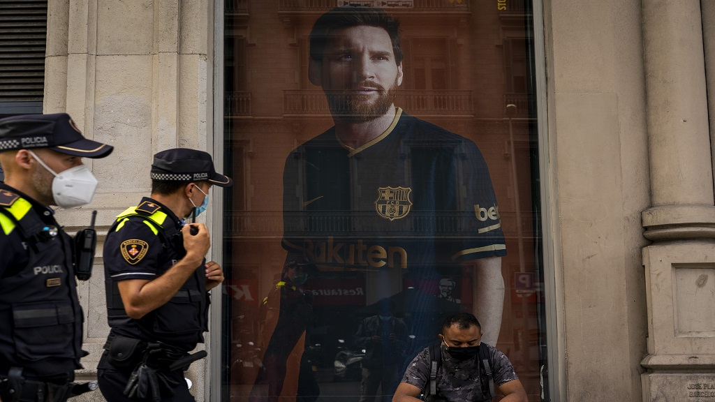 A poster with the face of Barcelona football player Lionel Messi is displayed at a F.C. Barcelona store in Barcelona, Spain on Tuesday, Sept. 1, 2020.  (AP Photo/Emilio Morenatti).