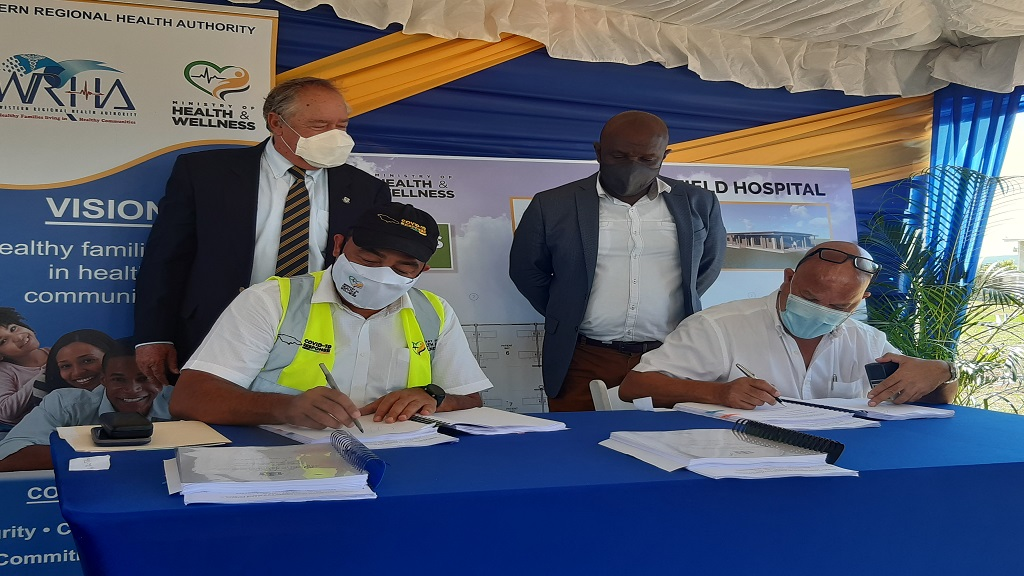 Health Minister, Dr Christopher Tufton, and a representative from Rogers Land Development Limited sign a contract for the construction of two field hospitals for the treatment of COVID-19 patients during a ceremony at the Falmouth Public General Hospital in Trelawny on Friday. Looking on are Custos of Trelawny, Paul Muschett (standing left) and Falmouth Mayor, Colin Gager.