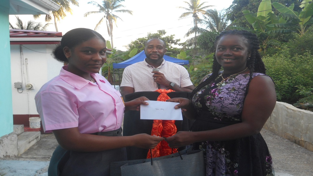 Tasha Phillip of the Vieux-Fort Comprehensive Secondary School (left) receiving her cheque and school supplies