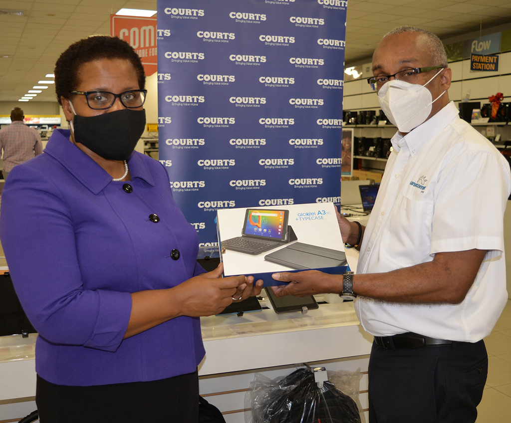 Dr. Sharon Anderson-Morgan; Assistant Chief Education Officer for the Ministry of Education (MOE) - left, and Managing Director, Unicomer Jamaica, Dennis Harris- right, take a moment to examine 1 of the Alcatel tablets donated to the MOE, at the Courts Cross Roads store.