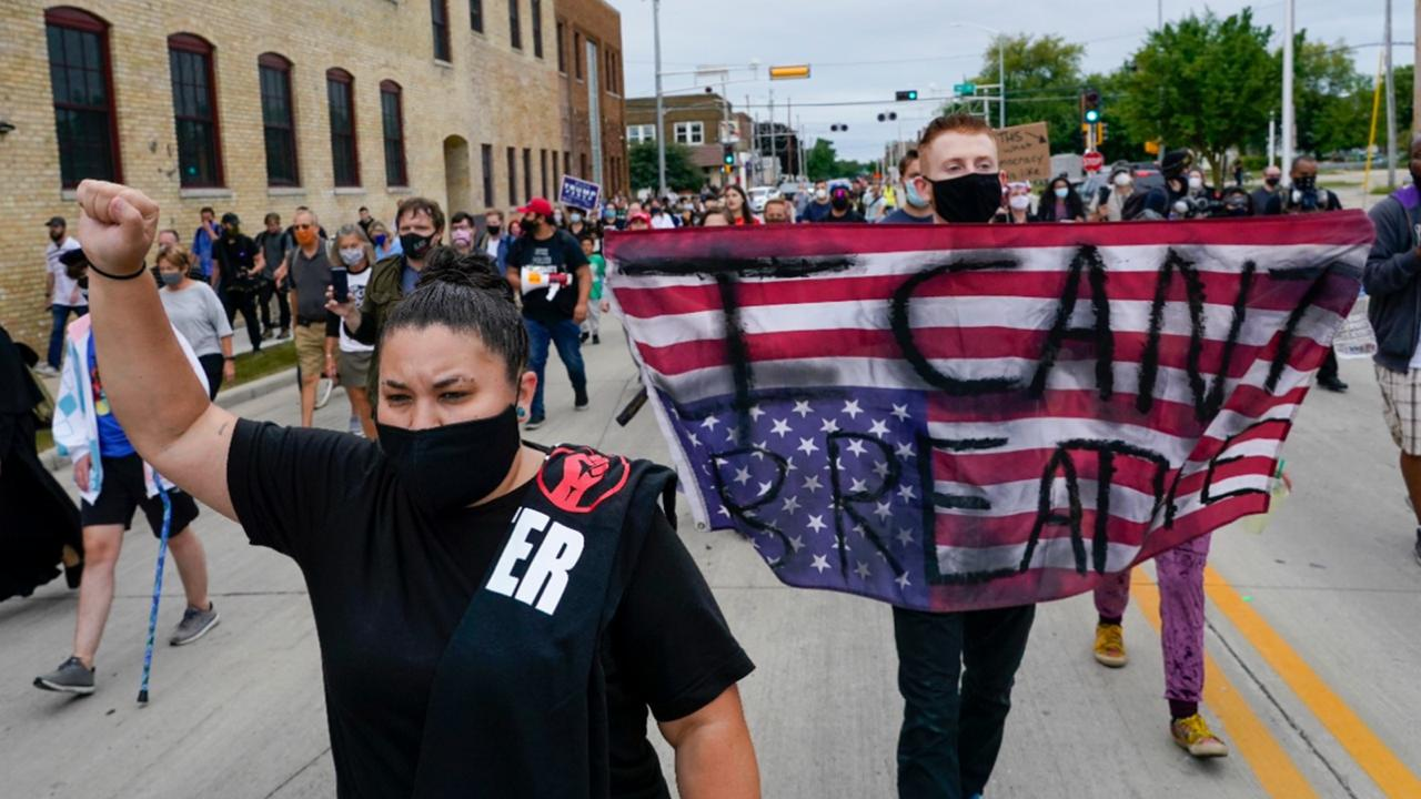 A protester holds a flag during a Black Lives Matter march Tuesday, Sept. 1, 2020, in Kenosha, Wis. (AP Photo/Morry Gash)