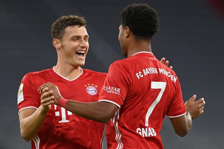 Le milieu du Bayern Munich, Serge Gnabry (d), auteur d'un triplé, félicité par le défenseur Benjamin Pavard lors de la victoire à domicile sur Schalke, le 18 septembre 2020 CHRISTOF STACHE AFP
