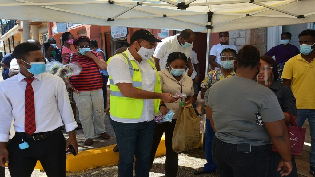 Minister of Health and Wellness, Dr Christopher Tufton (centre, foreground), hands out face masks and health information to residents in Falmouth, Trelawny on Friday, September 25.
