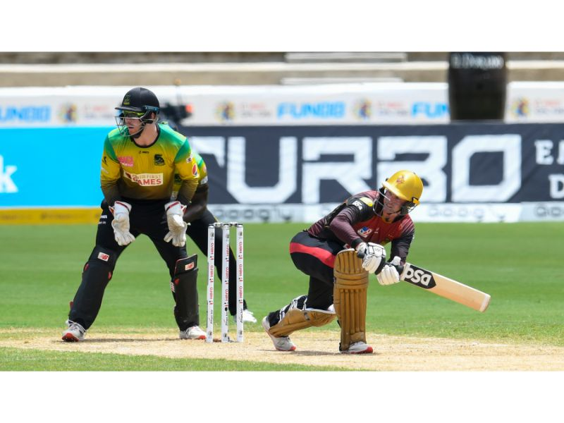 Trinbago Knight Riders' Colin Munro sweeps, watched by Jamaica Tallawahs wicketkeeper Glenn Phillips during Match 21 of the Hero Caribbean Premier League at the Brian Lara Cricket Academy, Tarouba, on 1st September 2020. (Photo by Randy Brooks - CPLT20/Getty Images)
