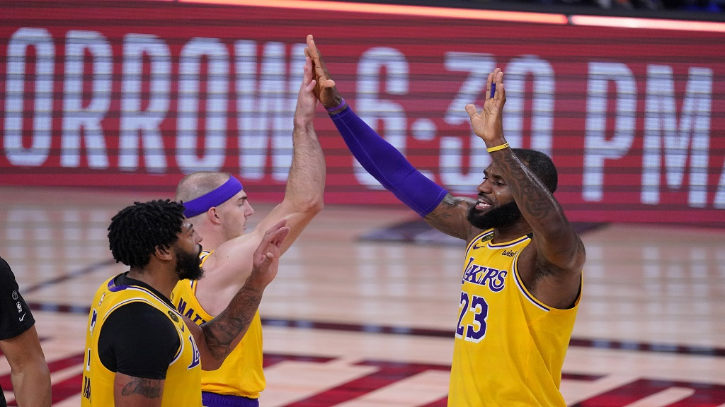 Los Angeles Lakers' LeBron James (23) celebrates with Anthony Davis, left, and Alex Caruso after an NBA conference semifinal playoff basketball game against the Houston Rockets Thursday, Sept. 10, 2020, in Lake Buena Vista, Fla. The Lakers won 110-100. (AP Photo/Mark J. Terrill).