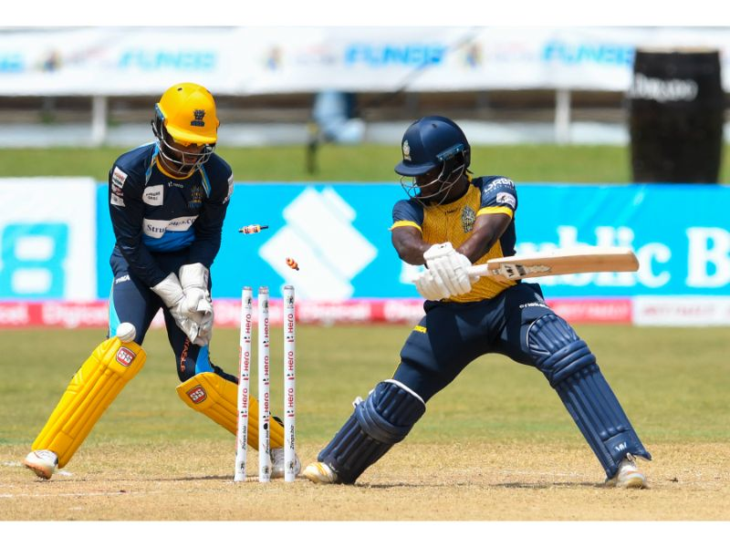 St Lucia Zouks opener Andre Fletcher is bowled during their narrow win over the Barbados Tridents on 30th August 2020 at the Queen's Park Oval in Game 19 of the 2020 Hero Caribbean Premier League. Tridents keeper Kyle Hope (right) watches on. (Photo by Randy Brooks - CPL T20/Getty Images)