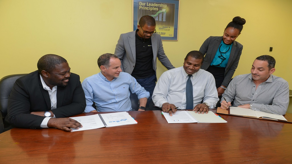 Reshando Mais (second right),Chief Financial Officer Tropical Battery, is joined by (seated L-R) Stanley Thompson, Manager Origination & Structuring NCBCM, Alexander Melville, Managing Director and Daniel Melville Director, Sales and Marketing Manager both of Tropical Battery as well as NCBCM pair (standing L-R) Robert Phillip, Trading Manager and Chivel Greenland, Junior Research Analyst, as he prepares to sign a brokerage partnership with NCB Capital Markets.