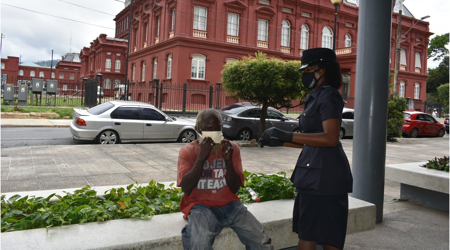 A police officer gives a mask to a homeless person in Port-of-Spain.