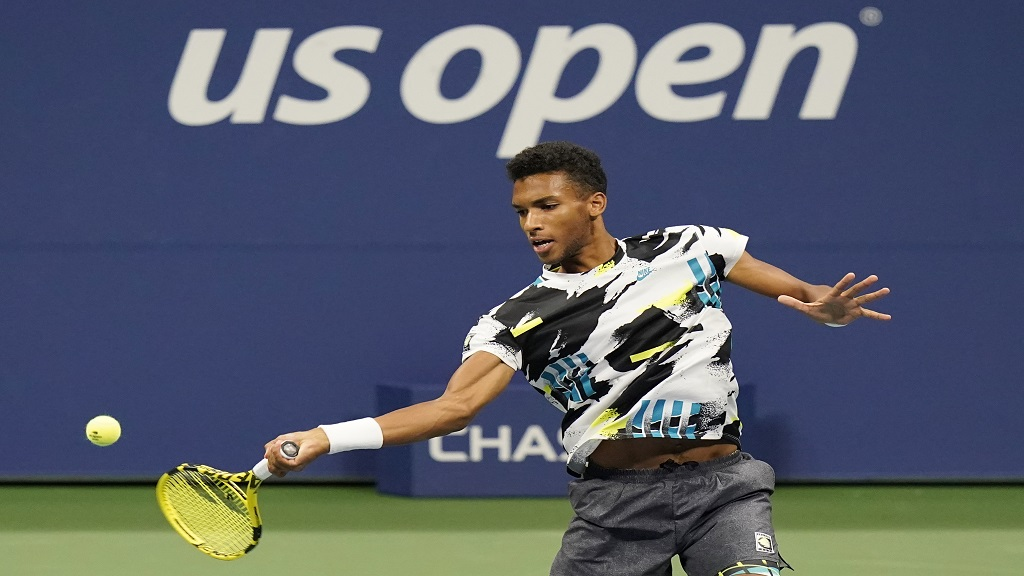 Felix Auger-Aliassime, of Canada, returns a shot to Andy Murray, of Great Britain, during the third round of the US Open tennis championships, Thursday, Sept. 3, 2020, in New York. (AP Photo/Frank Franklin II).