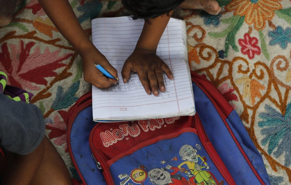 A child practices writing numbers on a blanket during the sidewalk classes. (AP Photo/Manish Swarup)