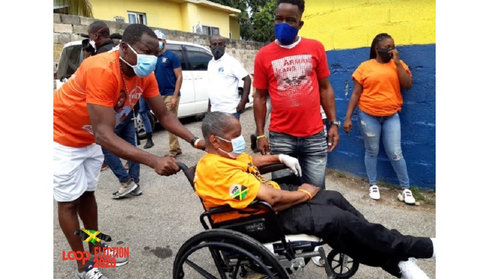 A wheelchair-bound People's National Party supporter being assisted by a fellow Comrade on Election Day.