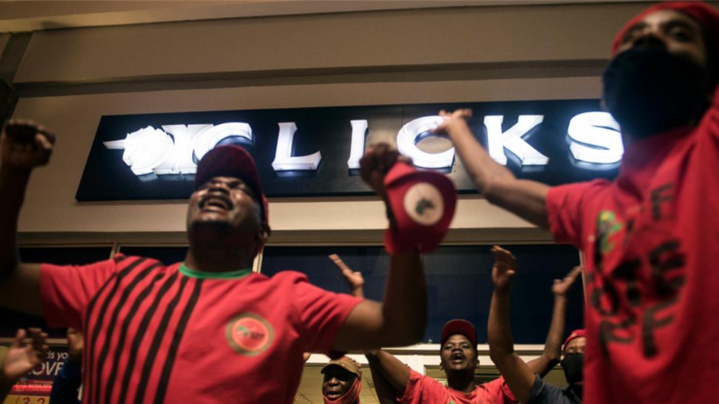 "Economic Freedom Fighters (EFF) supporters protest outside a Clicks store in Soweto, Johannesburg, Monday, Sept. 7 2020 calling for the closure of the stores around the country. The chain store posted an advertisement on their website that negatively described natural Black hair labelled as being ""Dry and Damaged"" and ""Frizzy and Dull"", while white people's hair was called ""Fine and Flat"" and ""Normal"". (AP Photo/Shiraaz Mohamed)"