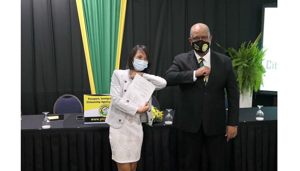 Shwe Thinza Aung (Myanmar) accepts her citizenship certificate from PICA CEO, Andrew Wynter, at a ceremony hosted by the Passport, Immigration and Citizenship Agency at the Knutsford Court Hotel in St Andrew.