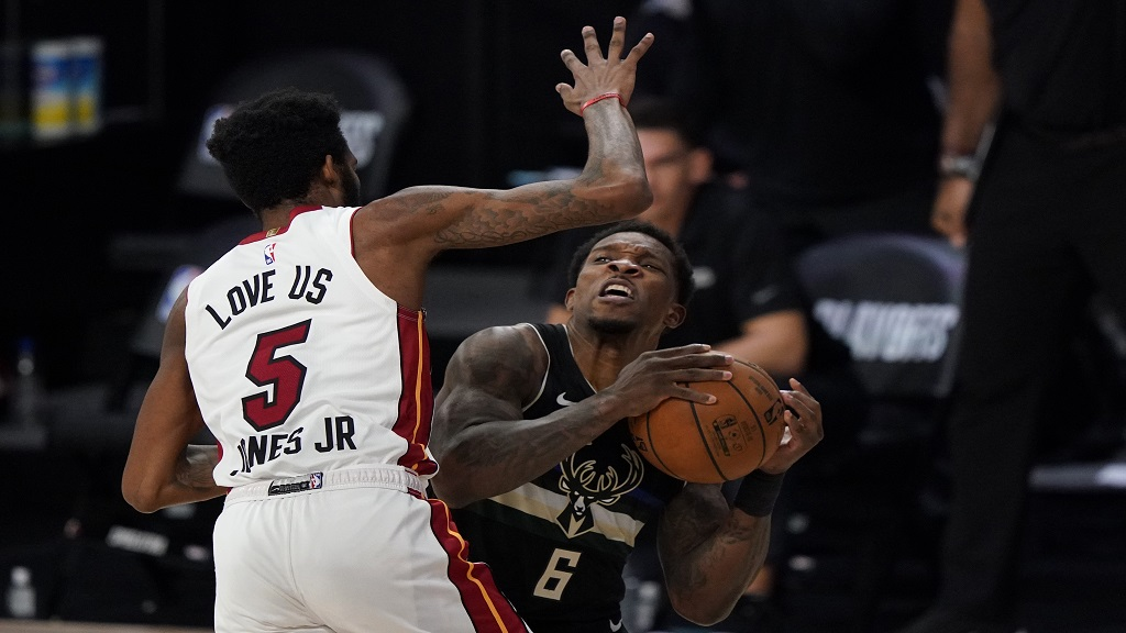 Miami Heat's Derrick Jones Jr. (5) moves to block a shot by Milwaukee Bucks' Eric Bledsoe (6) during the second half of an NBA conference semifinal playoff basketball game Wednesday, Sept. 2, 2020, in Lake Buena Vista, Fla. The Heat won 116-114. (AP Photo/Mark J. Terrill).