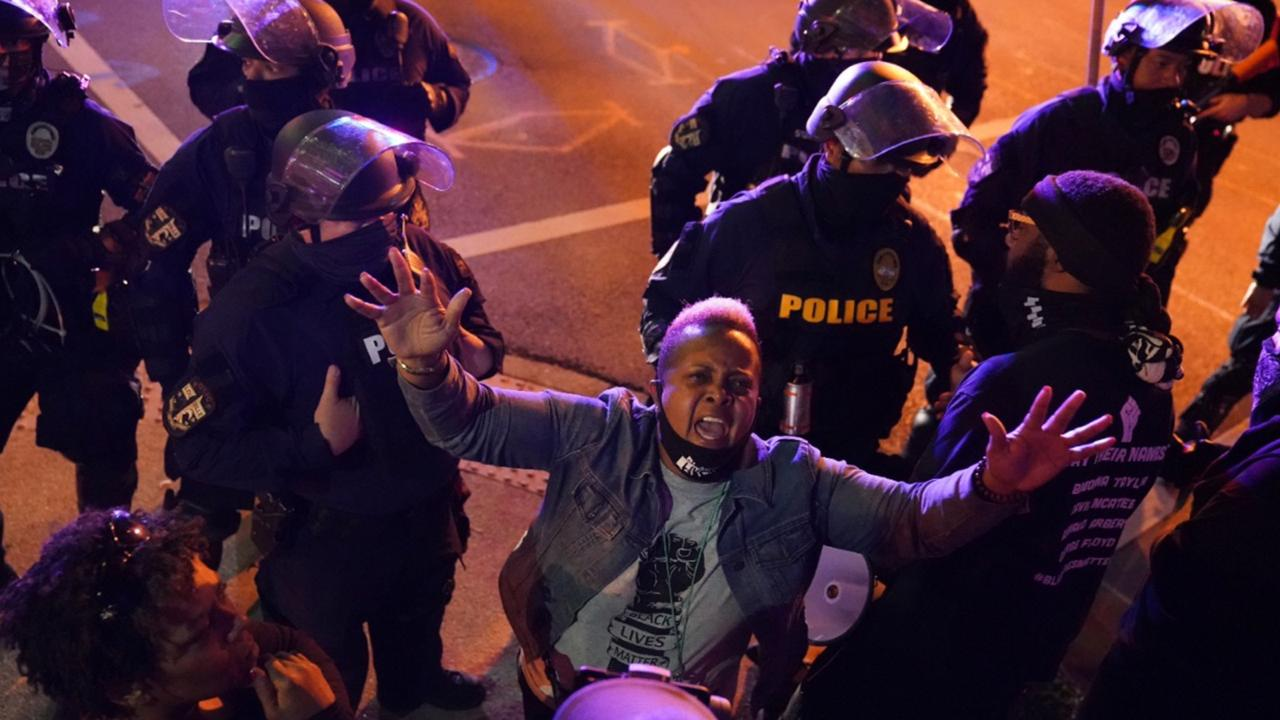 A woman speaks to police as protesters stay on church property, Thursday, in Louisville. Authorities pleaded for calm while activists vowed to fight on Thursday in Kentucky's largest city, where a gunman wounded two police officers during anguished protests following the decision not to charge officers for killing Breonna Taylor. (AP Photo/John Minchillo)