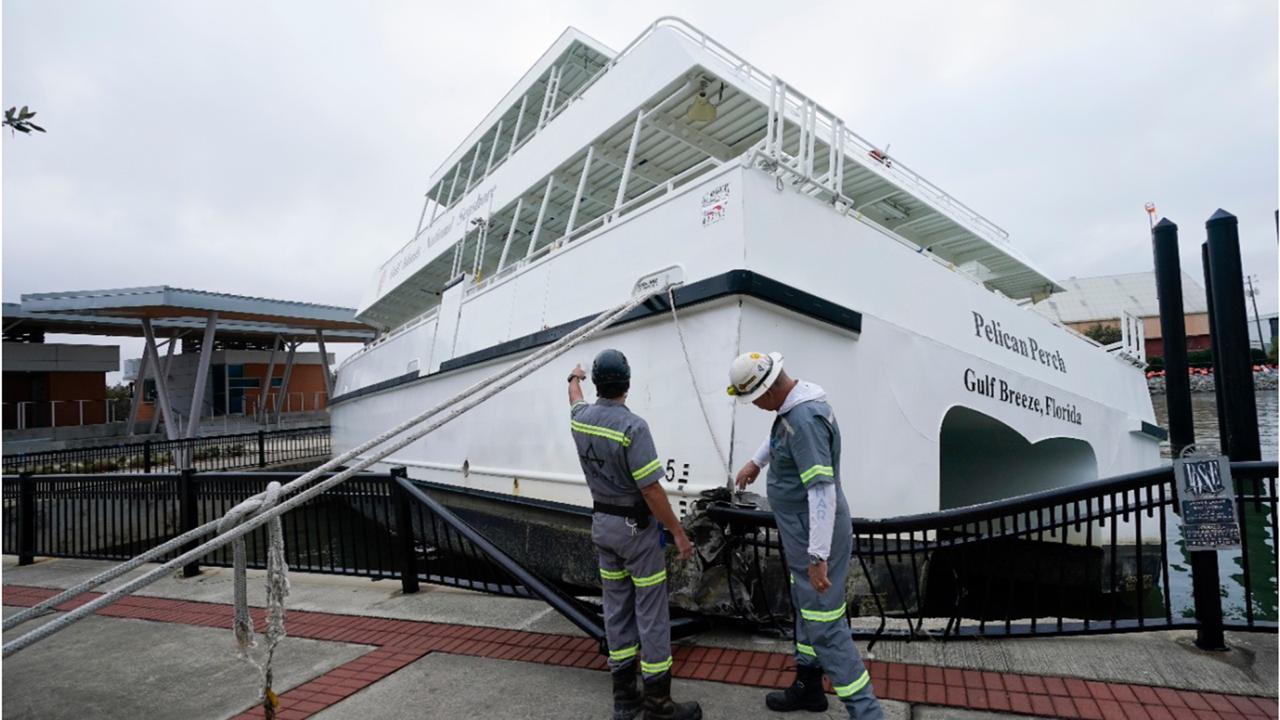 Workers look over a damaged ferry , Thursday, September 17, 2020, in Pensacola, Florida. Rivers swollen by Hurricane Sally's rains threatened more misery for parts of the Florida Panhandle and south Alabama on Thursday, as the storm's remnants continued to dump heavy rains inland that spread the threat of flooding to Georgia and the Carolinas.(AP Photo/Gerald Herbert)