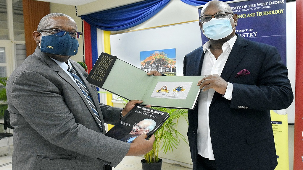 "(L-R) Professor Dale Webber, Pro Vice-Chancellor and Principal of The UWI Mona Campus and Dr Conrad Douglas, Alumnus and former President of the Chemistry Department Alumni Association, CHEMSAF, pictured holding the two special publications: ""The Department of Chemistry, UWI, Mona"" and ""From Logwood to Slowpoke: a Biography of Professor Gerald Lalor""."