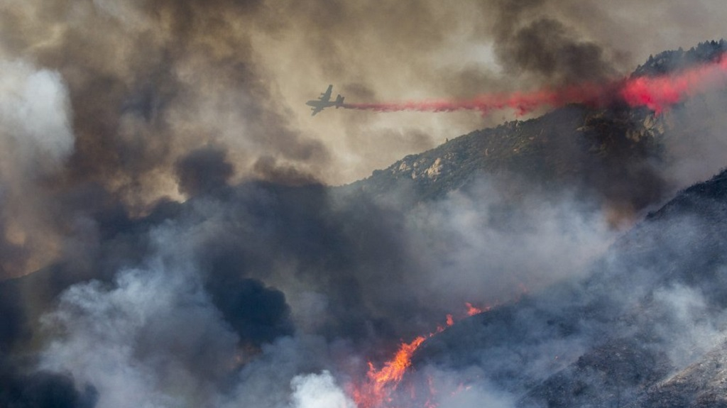 FILE - In this Saturday, September 5, 2020 file photo, an air tanker drops fire retardant on a hillside wildfire in Yucaipa, California. (AP Photo/Ringo H.W. Chiu)