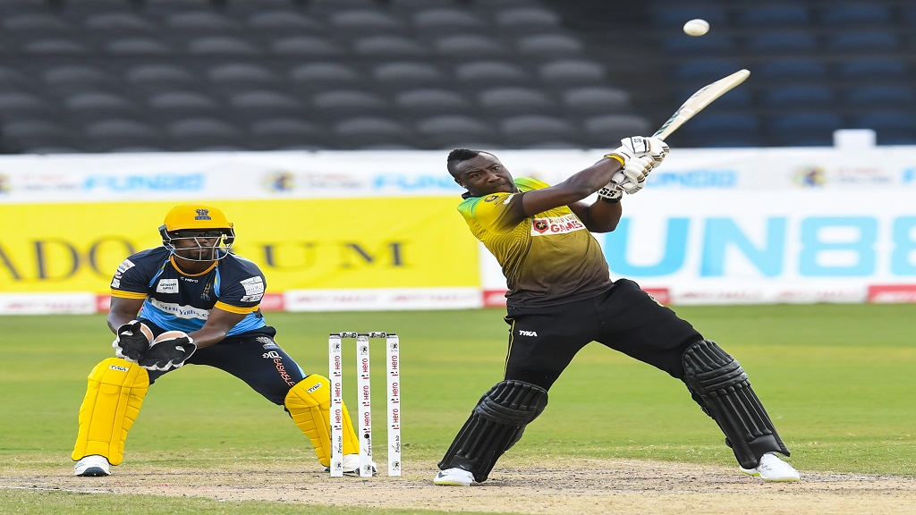 Andre Russell (R) of Jamaica Tallawahs hits a six, while wicketkeeper Johnson Charles of Barbados Tridents watches during match 28 of the Hero Caribbean Premier League, at the Brian Lara Cricket Academy in in Tarouba, Trinidad, on Saturday, September 5, 2020  (Photo by Randy Brooks - CPL T20/CPL T20 via Getty Images).