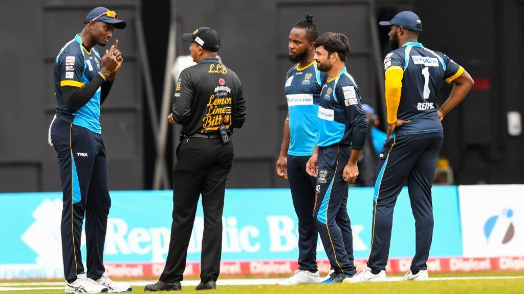 Jason Holder (L), Kyle Mayers (C), Rashid Khan (2R) and Raymon Reifer (R) of Barbados Tridents talk with umpire Joel Wilson (2L) during the Hero Caribbean Premier League match 5 between St Lucia Zouks and Barbados Tridents at Brian Lara Cricket Academy on August 20, 2020 in Tarouba, Trinidad And Tobago. (Photo by Randy Brooks - CPL T20/CPL T20 via Getty Images)