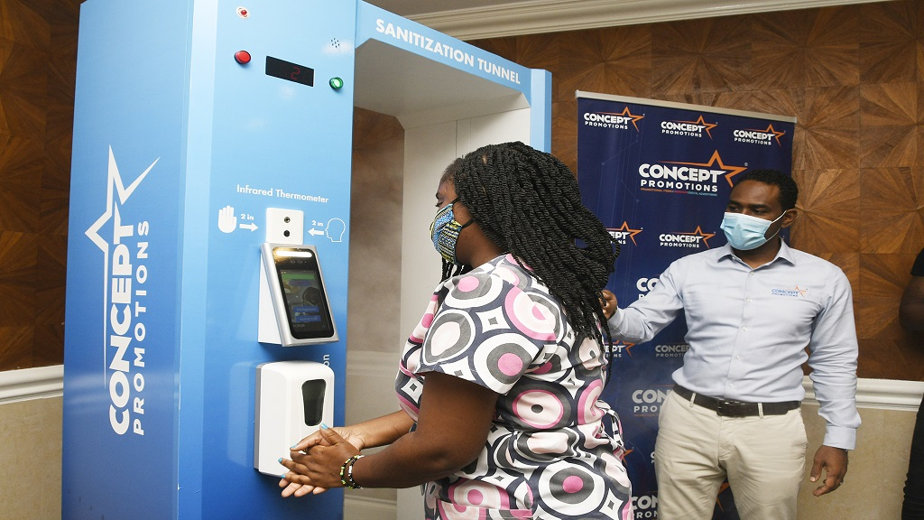 Itelbpo representative, Natasha Peart, is assisted by Adriel McKay (right), Founder and Managing Director of local branding company, Concept Promotions, as she does a facial recognition scan and gets her temperature checked during a demonstration exercise on the use of the device.