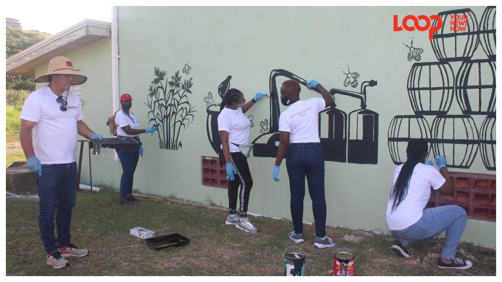 Mount Gay employees add the finishing touches to a mural on the wall of the refurbrished Charles Griffith Sports Centre as Managing Director Raphaël Grisoni looks on