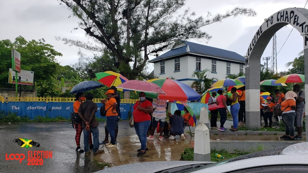 Voters takes shelter under umbrellas amid torrential rains in North Central Clarendon.