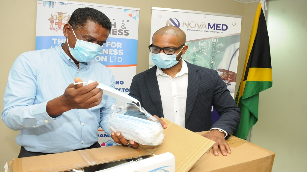 Executive Director of the Ministry of Health and Wellness' (MOHW) Health for Life and Wellness Foundation, Courtney Cephas (left) unpacks one of the 3-ply surgical-grade face masks donated by Founder of NovaMed, Dr David Walcott (right) to the Ministry of Health and Wellness.