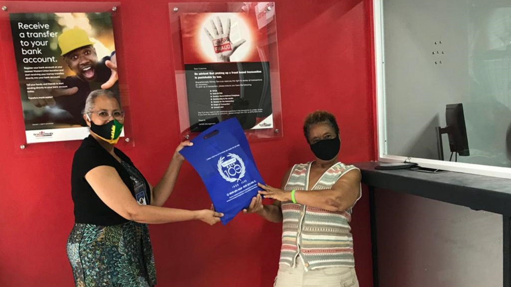 Francine Haughton (L), Company Director - 1920 Investments Limited, hands over a Haughton's Rx 100th Anniversary goodie bag to the first customer to successfully complete a transaction at the newly opened Western Union outlet located directly beside Haughton's Pharmacy in Mandeville.