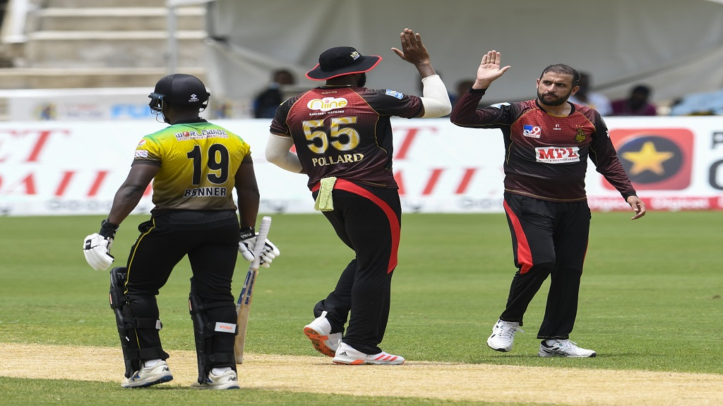 Trinbago Knight Riders' Fawad Ahmed (right) and captain Kieron Pollard celebrate the dismissal of Nkrumah Bonner (left) of Jamaica Tallawahs 