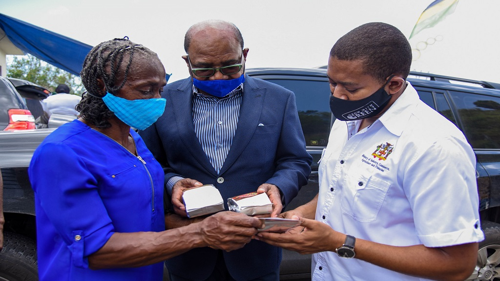Ministers Edmund Bartlett (centre) and Floyd Green , along with a product stakeholder, examine the new Blue Mountain Coffee 'teabag' product.
