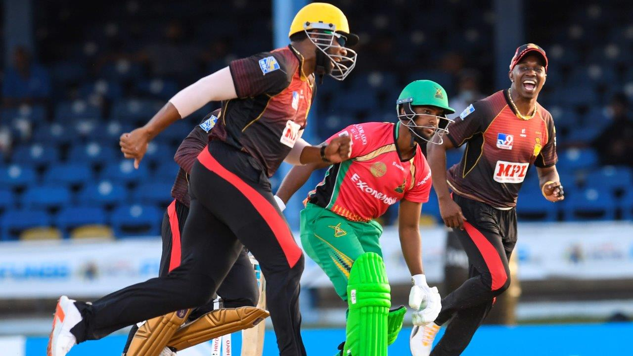 Kieron Pollard (L) and Dwayne Bravo (R) of Trinbago Knight Riders celebrate the dismissal of Nicholas Pooran (C) of Guyana Amazon Warriors during the Hero Caribbean Premier League match 16 between Guyana Amazon Warriors and Trinbago Knight Riders at Queen's Park Oval on August 27, 2020 in Port of Spain, Trinidad And Tobago. (Photo by Randy Brooks - CPL T20/CPL T20 via Getty Images)