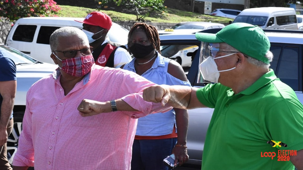 Opposition Leader Dr Peter Phillips and the ruling Jamaica Labour Party incumbent in the North East St Andrew constituency, Delroy Chuck, elbow bump on Thursday during the general elections.