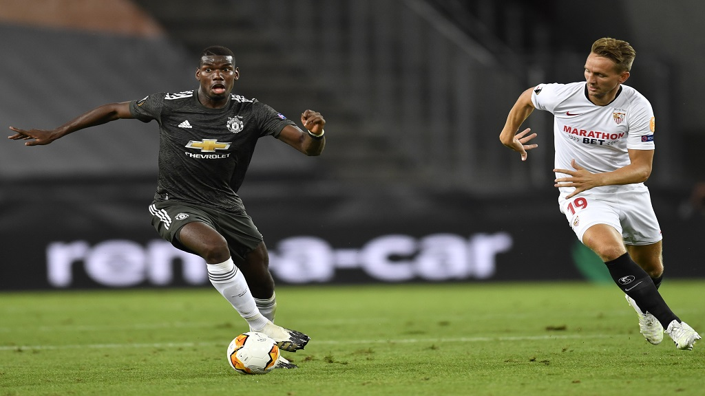 Manchester's Paul Pogba, left, and Sevilla's Luuk de Jong challenge for the ball during the UEFA Europa League semifinal match in Cologne, Germany, Sunday, Aug. 16, 2020. (Marius Becker/dpa via AP).