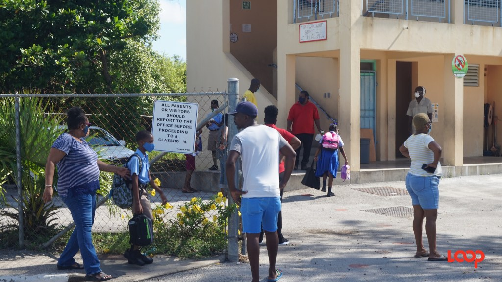 Parents dropping off their children at Reynold Weekes Primary on the first day of the school year (September 21).
