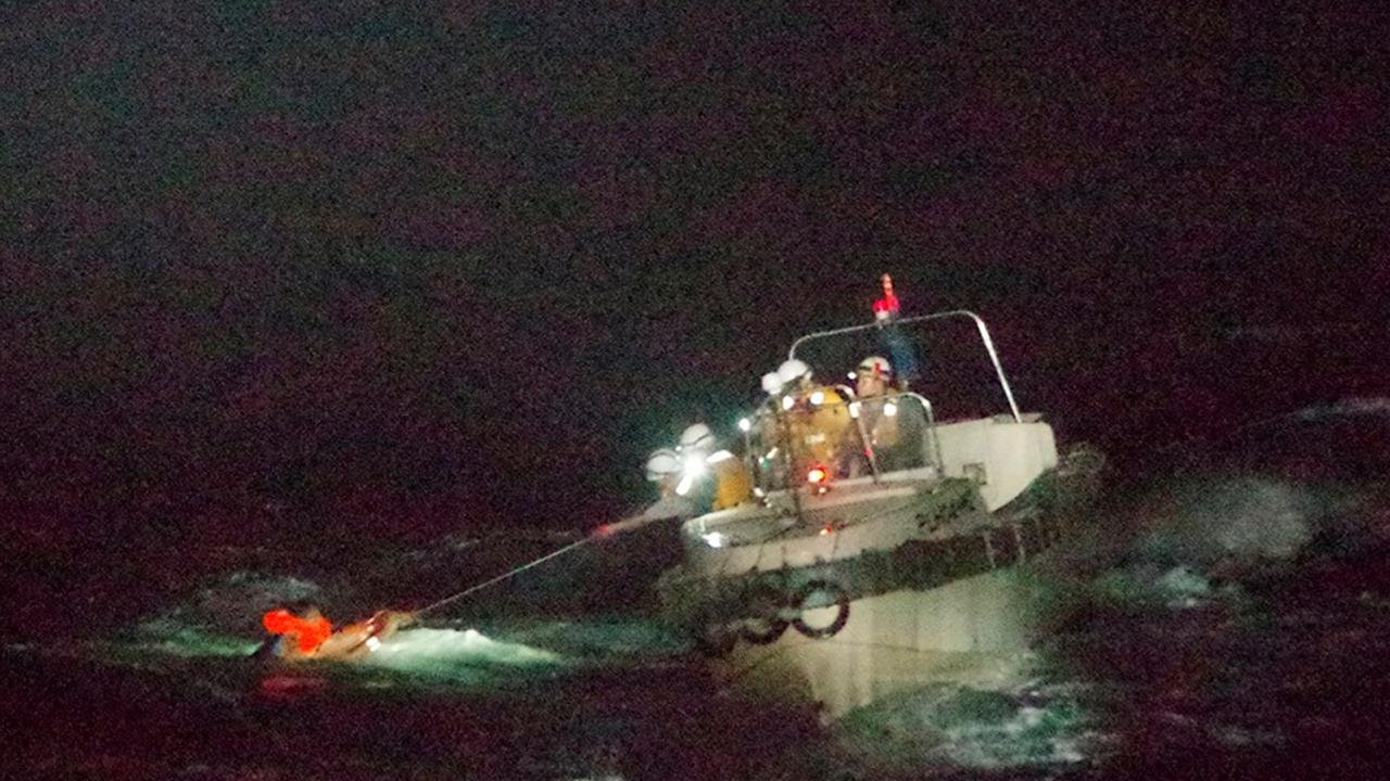 In this photo released by the 10th Regional Japan Coast Guard Headquarters, a Filipino crewmember of a Panamanian cargo ship is rescued by Japanese Coast Guard members in the waters off the Amami Oshima, Japan Wednesday, Sept. 2, 2020. (The 10th Regional Japan Coast Guard Headquarters via AP)