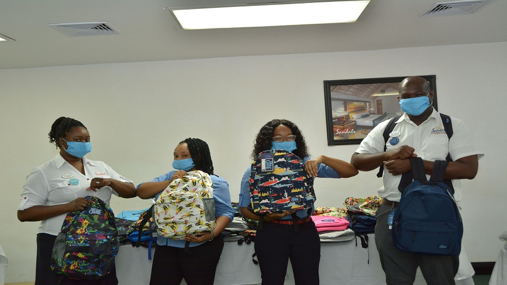 Sandals Negril's Hotel Manager O'Brian Heron (right) joins Human Resources Manager, Tameca Sutherland-Franklyn (left) in distributing back to school packages to team members Francia Stephenson (second left) and Onetta Allen.