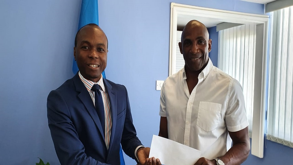Tourism Minister Dominic Fedee receives the donation from Cabot Saint Lucia Financial Controller Michael Mathius