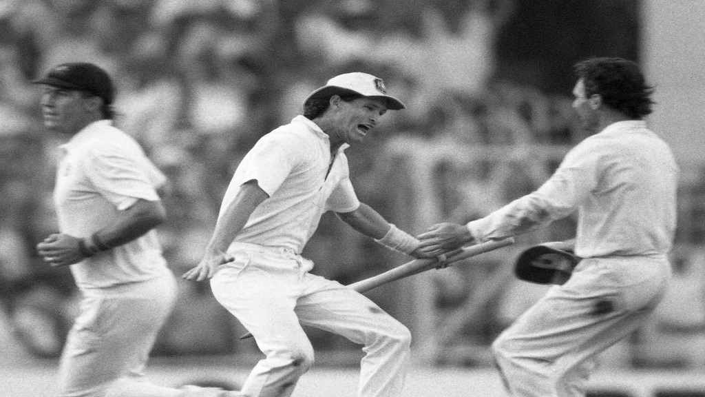 In this Nov. 8, 1987 file photo, Australian batsman Dean Jones holds the stumps as he races to embrace team captain Allan Border, right, in a moment of jubilation, in Calcutta, India. Jones has died of an apparent heart attack while in India to commentate on the Indian Premier League, it was reported on Thursday, Sept. 24, 2020. (AP Photo/Liu Heung Shing, File).