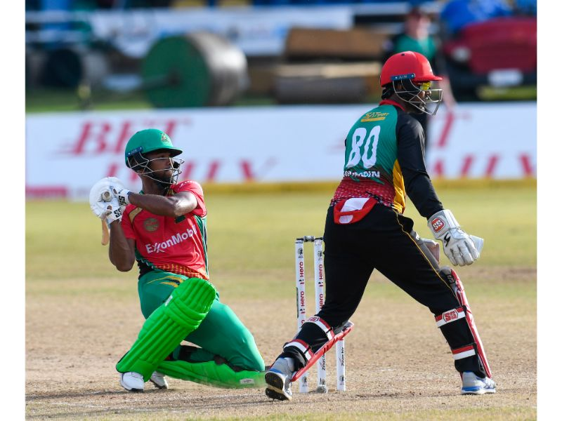 Guyana Amazon Warriors batsman Nicholas Pooran sweeps for six as St Kitts and Patriots wicketkeeper Denesh Ramdin watches on during Match 20 of the 2020 Hero Caribbean Premier League on Sunday at the Queen's Park Oval. (Photo by Randy Brooks - CPL T20/Getty Images)